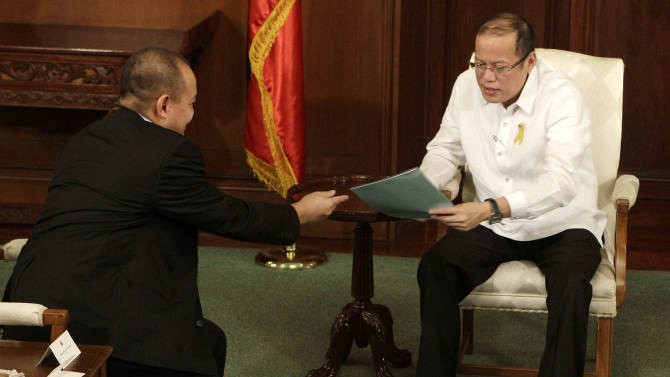 Philippine President Benigno Aquino III, right, receives documents from Philippine government negotiator Marvic Leonen during their meeting at the Malacanang presidential palace in Manila, Philippines on Monday, Oct. 8, 2012. The Philippine government and the country's largest Muslim rebel group reached a preliminary peace deal that is a major breakthrough toward ending a decades-long insurgency that killed tens of thousands and held back development in the south. (AP Photo/Aaron Favila)
