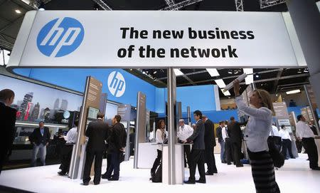 A visitor takes a photo with a tablet in front of a Hewlett-Packard (HP) stand at the Mobile World Congress in Barcelona