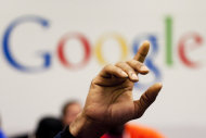 FILE - In this Oct. 17, 2012, file photo, a man raises his hand during at Google offices, Oct. 17, 2012. The world's attention veered from the tragic to the silly in 2012, and along the way, Web surfers searched in huge numbers to find out about a royal princess, the latest iPad, Mother Nature's wrath and a record-breaking skydiver. (AP Photo/Mark Lennihan)