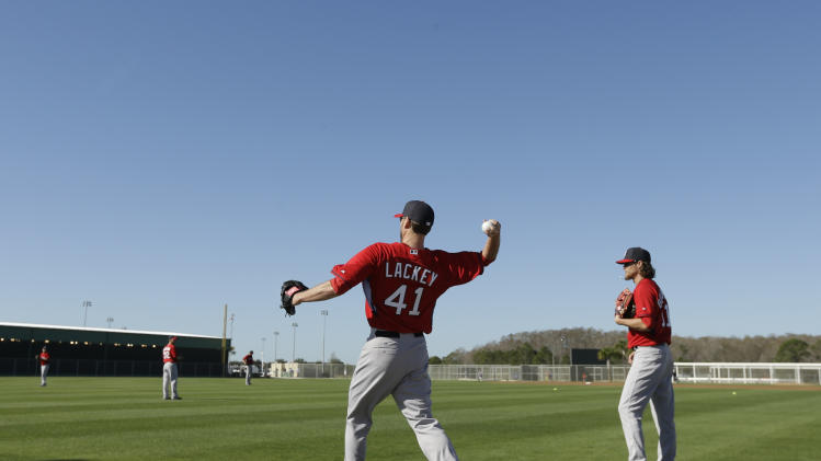 Boston Red Sox starting pitcher John Lackey, center, warms up on the field during spring training baseball practice Monday, Feb. 17, 2014, in Fort Myers, Fla. Boston Red Sox starting pitcher Clay Buchholz stands right. (AP Photo/Steven Senne)