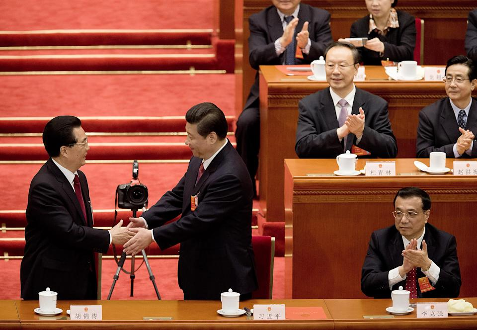 Newly-named Chinese President Xi Jinping, center, is greeted by outgoing President Hu Jintao, left, as Vice Premier Li Keqiang, right, and delegates applause at a plenary session of the National People's Congress held at the Great Hall of the People in Beijing Thursday, March 14, 2013. (AP Photo/Andy Wong)