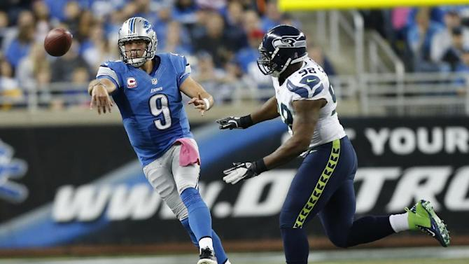 Detroit Lions quarterback Matthew Stafford (9) passes as Seattle Seahawks defensive end Greg Scruggs (98)approaches in the second half of an NFL football game, Sunday, Oct. 28, 2012. in Detroit. (AP Photo/Rick Osentoski)
