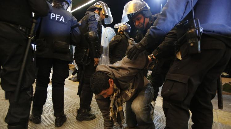 Police officers detain a man after riot police fired tear gas and used water cannons to restrain a group of youths who hurled rocks and vandalized store fronts at a rally to celebrate Argentina's gutsy performance in a 1-0 loss to Germany in the World Cup finals, in Buenos Aires, Argentina, Sunday, July 13, 2014. The chaotic situation marred what was an otherwise spontaneous gathering of support for Argentina's national team after its best World Cup run in 24 years. (AP Photo/Jorge Saenz)
