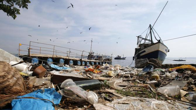 Garbage is seen near a fishing boat on Fundao beach in the Guanabara Bay in Rio de Janeiro
