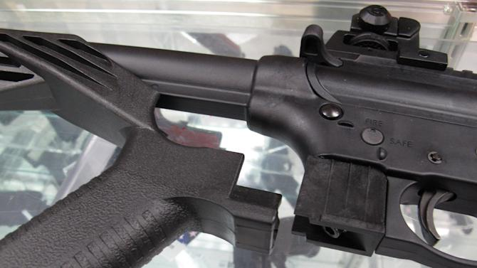 """This Feb. 1, 2013 photo shows a """"bump"""" stock next to a disassembled .22-caliber rifle at North Raleigh Guns in Raleigh, N.C. The accessory devices, which legally allow a semiautomatic rifle to fire like a real machine gun, are among nearly 160 weapons or accessories targeted by a proposed federal ban. (AP Photo/Allen Breed)"""