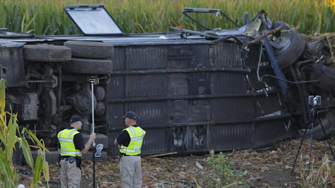 Ohio High Highway Patrol investigators on the scene of a Greyhound bus travailing from Cincinnati to Detroit Saturday Sept. 14, 2013, with 52 passengers on board left the highway and crashed in Liberty Township, between State Rt. 129 and the Monroe Exit at St. Rt.63, 34 passengers where taken to area hospitals, according to the Butler County Sheriff's Office only 2 of 3 northbound of Interstate 75 are open. (AP Photo/The Enquirer, Tony Jones)