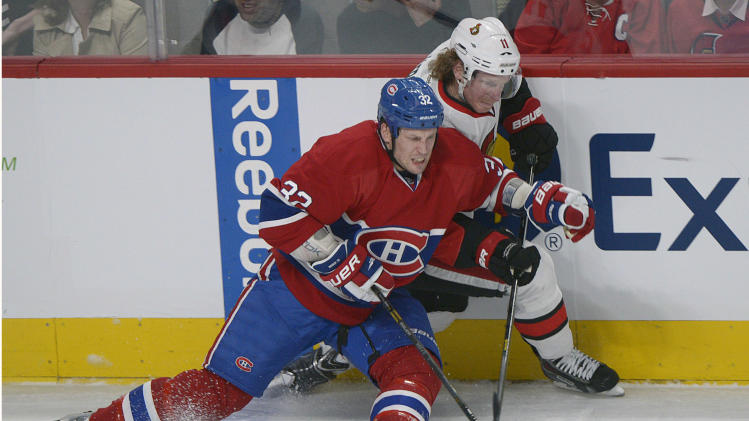 Ottawa Senators' Daniel Alfredsson (11) and Montreal Canadiens' Travis Moen fight for the puck during second-period NHL hockey Game 2 first-round playoff action in Montreal, Friday, May 3, 2013. (AP Photo/The Canadian Press, Graham Hughes)