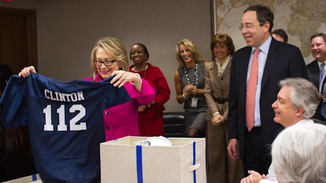 "This handout photo provided by the State Department shows Secretary of State Hillary Rodham Clinton holding up a football jersey, number ""112"" at the State Department in Washington, Monday, Jan. 7, 2013, as she returned to work on Monday after a month-long absence caused first by a stomach virus, then a fall and a concussion and finally a brief hospitalization for a blot clot near her brain. She was also given a blue football jersey with ""Clinton"" and the number 112 _ the record-breaking number of countries she has visited since becoming secretary of state _ printed on the back. (AP Photo/State Department)"