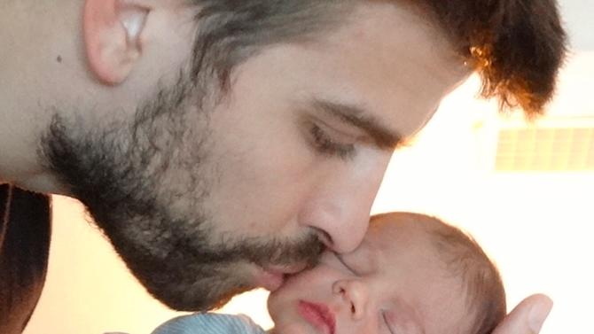 This undated image released courtesy of singer and UNICEF Goodwill Ambassador Shakira shows FC Barcelona star Gerard Piqué kissing the cheek of his son Milan, born Jan. 22 in Barcelona. The couple are inviting friends and fans to join their online baby shower to help provide life-saving items to children and communities in some of the poorest corners of the globe. After purchasing an Inspired Gift, they will then receive a personal thank you message from the couple. (AP Photo/courtesy of Shakira)