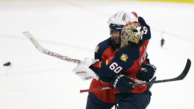 Florida Panthers' Ed Jovanovski (55) and goalie Jose Theodore (60) celebrate after the third period of Game 5 in a first-round NHL Stanley Cup playoff hockey series against the New Jersey Devils in Sunrise, Fla., Saturday, April 21, 2012. The Panthers won 3-0. Fans were throwing plastic rats onto the ice in celebration. (AP Photo/J Pat Carter)