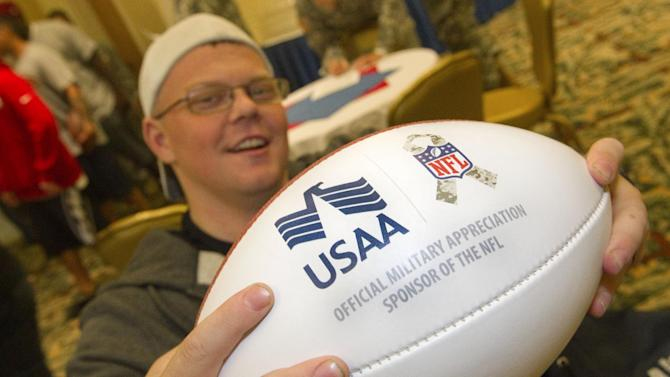 IMAGE DISTRIBUTED FOR USAA - William Thomas, a member of the Warrior Transition Battalion at Schofield Barracks, shows off his USAA NFL football Thursday, Jan. 24, 2013, in Honolulu. Thomas along with several other wounded soldiers had lunch and met six National League Football players whom are playing in this weekend's NFL Pro Bowl. (Eugene Tanner/AP Images for USAA)