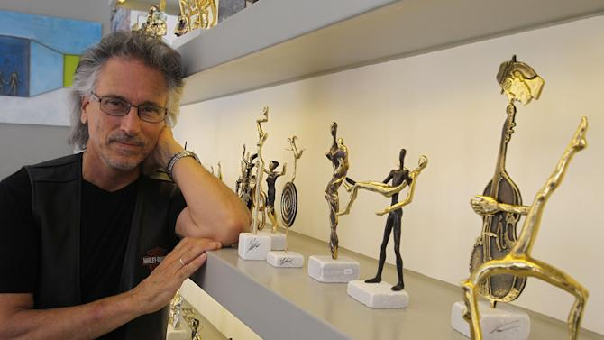 """The artist Yianni poses by his creations at his showroom in Athens, Friday, June 22, 2012. For at least two decades, artist Yanni Souvatzoglou has displayed his bronze sculptures in the old Athens neighborhood of Plaka. He depicts Dimitra, the goddess of fertility and agriculture, as a slender figure, like a stalk of wheat, with a symbolism that suits hard times. """"She told us to use our ingenuity to survive even if we don't have wheat,"""" said Souvatzoglou, who cites his main influences as the ancient Minoan and Cycladic eras. """"She told us, 'Before you do something important in your life, you should apply thinking' _ she's holding her head _ 'But if things don't work out for some reason, be flexible.' Like the wheat is when the wind is blowing."""" (AP Photo/Petros Karadjias)"""