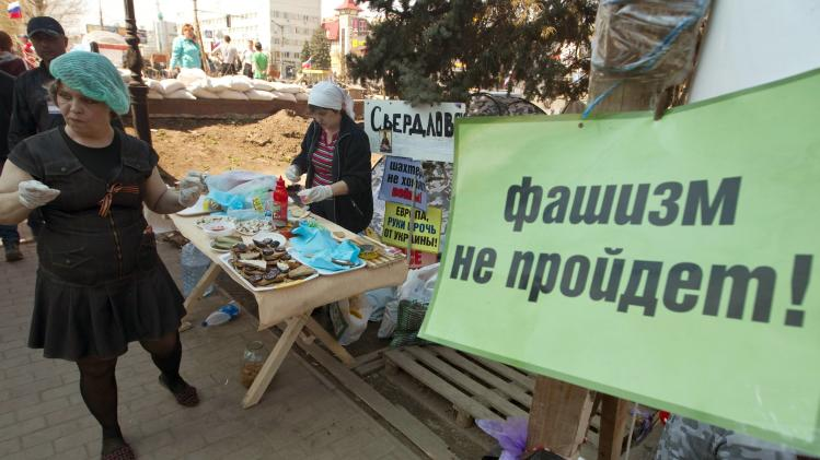 Pro-Russian supporters prepare food in their camp near the seized office of the SBU state security service in Luhansk