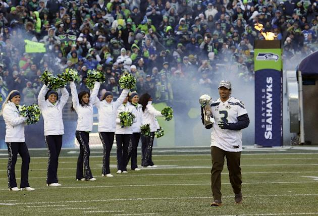 Seattle Seahawks quarterback Russell Wilson (3) carries the Vince Lombardi Trophy into CenturyLink Field as the Seahawks Sea Gals cheerleaders perform at the start of a rally on Wednesday, Feb. 5, 201