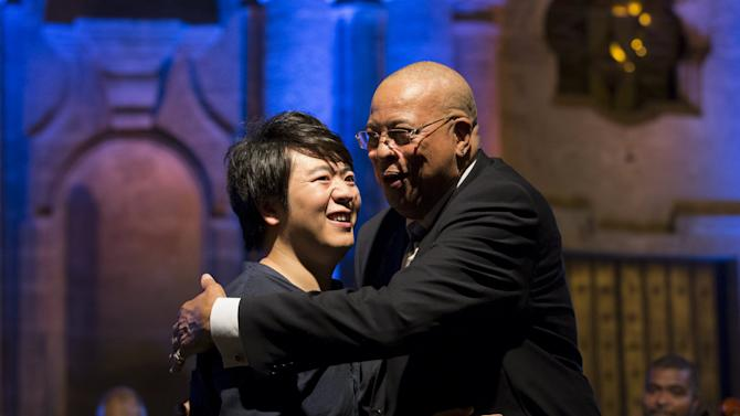 Cuban pianist and Grammy winner Chucho Valdes embraces pianist Lang Lang from China during a concert at the Cathedral Square in Havana
