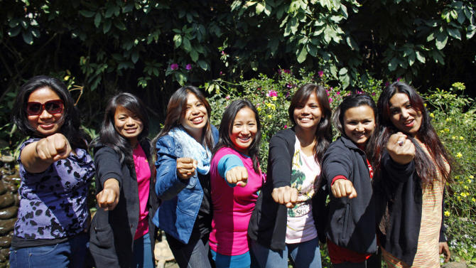 In this Tuesday, Feb. 21, 2013 photo, Nepalese climbers, from left, Maya Gurung, Nimdoma Sherpa, Chunu Shrestha, Pema Dikki, Asha Singh, Shailee Basnet and Pujan Acharya pose for photographs in Katmandu, Nepal. Aiming to change the all-male image of mountaineering in the country, a group of Nepalese women have embarked on a mission to climb the tallest mountain on each of the seven continents. The women, aged between 21 and 32, have already climbed Everest in Asia, Kosciuszko in Australia and Elbrus in Europe and are preparing next week to climb Mount Kilimanjaro in Africa to mark International Women's Day. (AP Photo/Niranjan Shrestha)