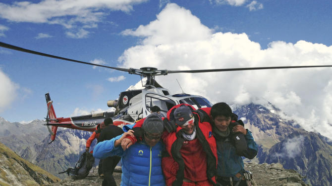 In this photo provided by Nepalese airline Simrik Air, an injured victim, center, of an avalanche is rescued at the base camp of Mount Manaslu in northern Nepal, Sunday, Sept. 23, 2012. The avalanche swept away climbers on a Himalayan peak in Nepal on Sunday, leaving at least nine dead and six others missing, officials said. (AP Photo/Simrik Air)