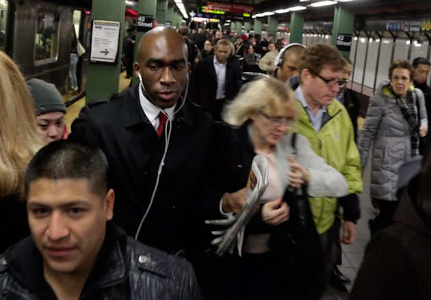 """In this photo taken March 14, 2013, morning commuters fill the platform as they exit a train in New York's Times Square subway station. An historic decline in the number of U.S. whites and the fast growth of Latinos are blurring traditional black-white color lines, testing the limits of civil rights laws and reshaping political alliances as """"whiteness"""" begins to lose its numerical dominance. The demographic shift is now a potent backdrop to an immigration overhaul bill being debated in Congress that could offer a path to citizenship for 11 million mostly Hispanic illegal immigrants. [AP Photo/Richard Drew)"""
