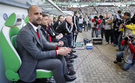 Bayern Munich head coach Pep Guardiola of Spain waits for the start of the German first division Bundesliga soccer match against Wolfsburg in Wolfsburg, March 8, 2014. REUTERS/Fabrizio Bensch