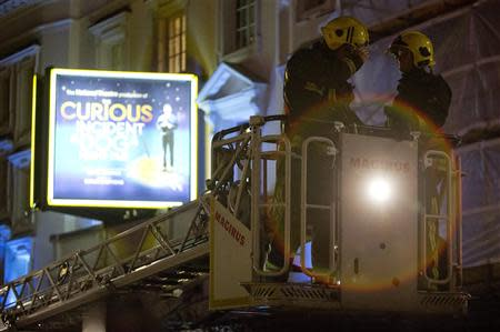 Emergency services use a cherry picker to look at the roof of the Apollo Theatre on Shaftesbury Avenue after part of the ceiling collapsed in central London