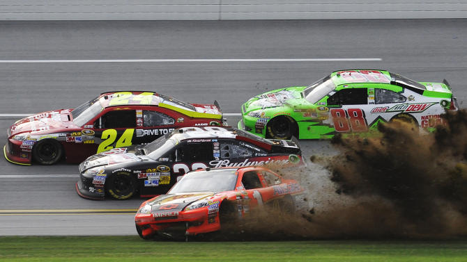 Jamie McMurray (1) kicks up dirt as he spins while Jeff Gordon (24), Kevin Harvick (29) and Dale Earnhardt Jr., (88) avoid damage during the NASCAR Sprint Cup Series auto race at Talladega Superspeedway in Talladega, Ala., Sunday, Oct. 7, 2012. (AP Photo/Rainier Ehrhardt)