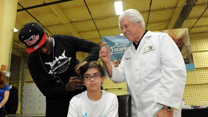 Carolina Panthers Brandon Lafell helps Bill Austin, founder of Starkey Hearing Foundation, fit a young girl with a hearing aid at The Citi Garth Brooks Super Pro Camp on Friday, Feb. 1, 2013 in New Orleans. (Photo by Cheryl Gerber/Invision for Starkey Hearing Foundation/AP Images)