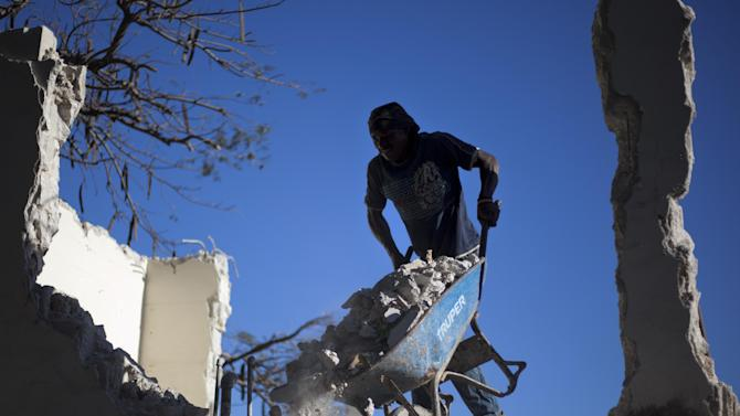 Edner Gue pushes a wheelbarrow filled with rubble as he works to clean up the earthquake damaged Grande College Auguste Comte de Petionville, in his neighborhood of Petionville, Haiti, Friday, Jan. 11, 2013.  The director of the elementary and high school is paying workers to clean up his school and plans to open classes even if the government does not rebuild it. On Saturday, Haiti will mark the 3rd anniversary of the earthquake that officials say killed more than 300,000 people and displaced more than a million others. The disaster is regarded as one of the worst natural disasters in modern history. (APPhoto/Dieu Nalio Chery)