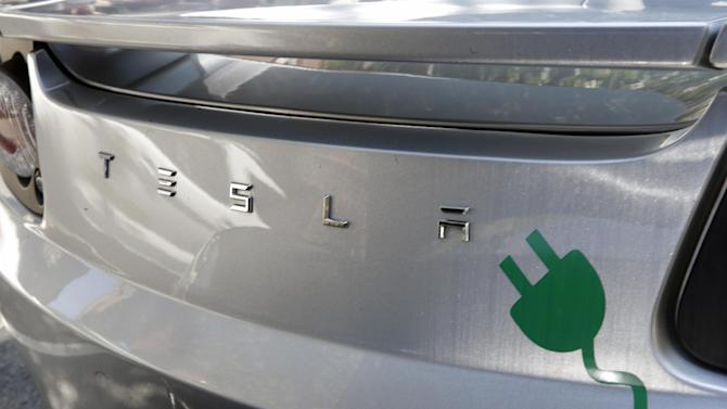 An electric plug decal is seen on the back of a Tesla electric car as owners, environmental and business advocates rally in front of the Statehouse, Monday, June 16, 2014, in Trenton, N.J., to call on legislators to pass a bill that will allow Tesla to resume sales in New Jersey. The Assembly unanimously approved a bill that would allow zero-emission carmakers to sell directly to consumers in New Jersey. The state Motor Vehicle Commissioner earlier this year approved regulations that require new-car dealers to have franchise agreements, effectively banning Tesla's business model. (AP Photo/Mel Evans)