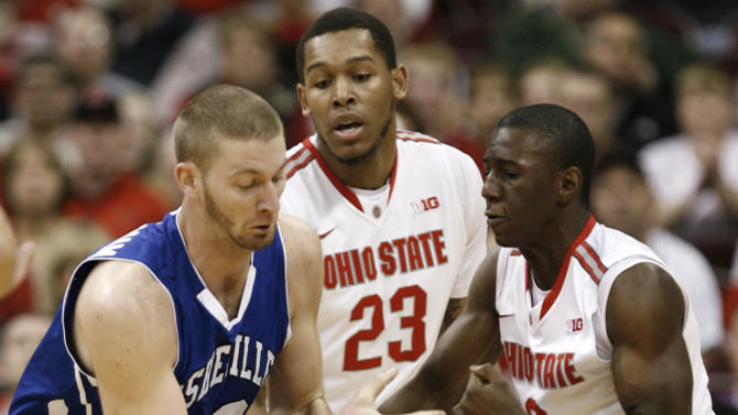 Ohio State's Shannon Scott, right, and teammate Amir Williams, center, try to steal the ball from UNC-Asheville's D.J. Cunningham during the first half of an NCAA college basketball game in Columbus, Ohio, Saturday, Dec. 15, 2012. (AP Photo/Paul Vernon)
