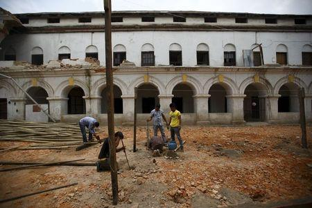 Laborers work to build a temporary classroom outside a damaged school, a month after the April 25 earthquake in Kathmandu, Nepal