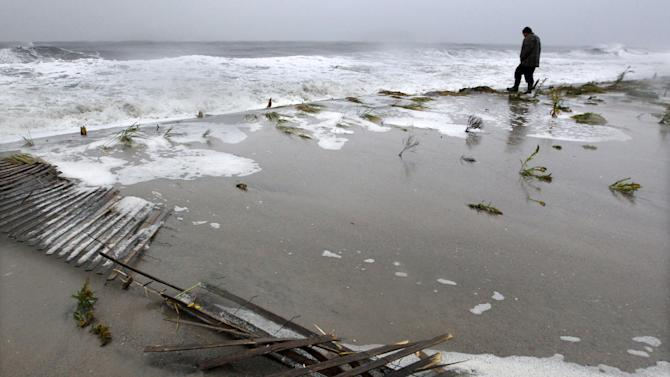 FILE - In this Monday, Oct. 29, 2012 file photo, a man walks along the beach near rough surf in the Atlantic Ocean in Cape May, N.J., as high tide and Superstorm Sandy begin to arrive. Humans have an affinity for water. But in these recent jumbled days, the collapsed houses, flooded subway tunnels and washed-out roads left in Sandy's wake remind us once again: Our deep-seated human desire to be near the water _ to be attracted and comforted by it, to build alongside it and crave its attractions _ has an undeniable dark side. (AP Photo/Mel Evans, File)