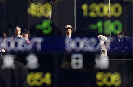 Pedestrians are reflected in an electronic board showing stock prices outside a brokerage in Tokyo