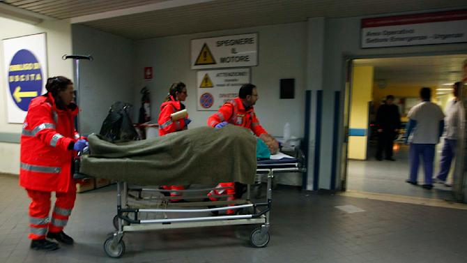 A person rescued from the Norman Atlantic vessel in the Adriatic sea is carried by medics off the ambulance as they arrive at the Antonio Perrino hospital in Brindisi