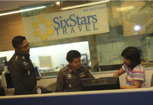 Policemen talk to a staff member of the Six Stars Travel in Pattaya, Chonburi province, Thailand, Monday, March 10, 2014. The agency told police that it had issued the tickets used by the holders of t
