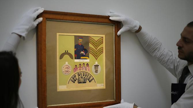 """FILE This Friday, Nov.  9, 2012 file photo shows employees from Sotheby's auction house adjust the original Sir Peter Blake 1967 collage for the iconic Beatles album Sgt Pepper's Lonely Hearts Club Band, which will be sold at  auction, during a press viewing in London. Sotheby's says an original piece of artwork from the Beatles' """"Sgt Pepper's Lonely Hearts Club Band"""" album has fetched 55,250 pounds ($87,720) at auction. The auction house said the original 1967 collage for the insert to the album sold to a bidder in London on Tuesday Nov.13, 2012. The sale marked the first time the collage by Sir Peter Blake was on the market.  The auction house said Blake was introduced to the Beatles by his dealer, and that he and his wife worked closely with Paul McCartney and John Lennon to create the imagery of the Sgt. Pepper.  (AP Photo/Alastair Grant, file)"""