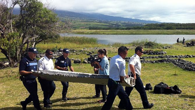 Police carry the Boeing 777 wing part on July 29, 2015, discovered on La Reunion island
