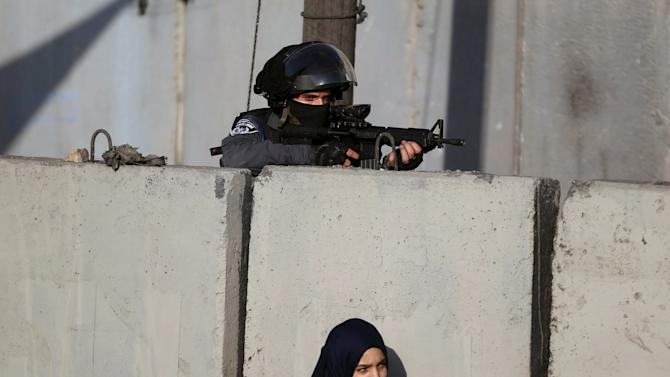 Israeli border policeman keeps guard as a Palestinian girl waits with her mother to show their permits to Israeli security officers at Qalandia checkpoint