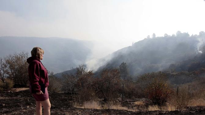 Dusty Hoetger watches as smoke rises from the Ponderosa Fire along Highway 36 near Paynes Creek, Calif., Thursday, Aug. 23, 2012. More than 2,400 firefighters are battling the Ponderosa Fire that has destroyed 64 homes and burned more than 27,000 acres. (AP Photo/Rich Pedroncelli)