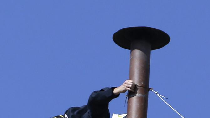 A firefighter places the chimney on the roof of the Sistine Chapel, where cardinals will gather to elect the new pope, at the Vatican, Saturday, March 9, 2013. The preliminaries over, Catholic cardinals are ready to get down to the real business of choosing a pope. And even without a front-runner, there are indications they will go into the conclave Tuesday with a good idea of their top picks. The conclave date was set Friday during a vote by the College of Cardinals, who have been meeting all week to discuss the church's problems and priorities, and the qualities the successor to Pope Benedict XVI must possess. (AP Photo/Gregorio Borgia)
