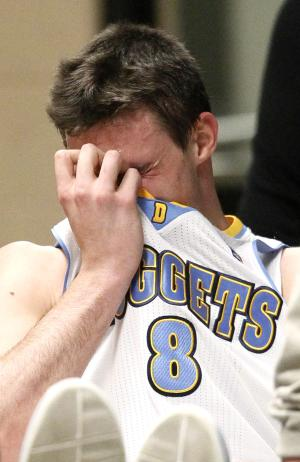 Denver Nuggets forward Danilo Gallinari, of Italy, uses his jersey to cover his face as he is wheeled to the team's locker room after being injured against the Dallas Mavericks in the second quarter of an NBA basketball game in Denver on Thursday, April 4, 2013. (AP Photo/David Zalubowski)