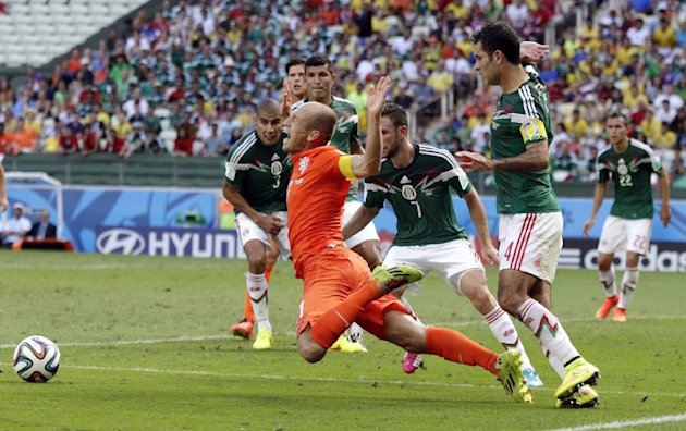 Netherlands' Arjen Robben, center, goes down to win a penalty during the World Cup round of 16 soccer match between the Netherlands and Mexico at the ...