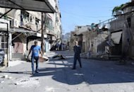 Syrian men walk through a heavily damaged street in the Damascus suburb of Tadamun, the scene of heavy fighting which was retaken by government troops