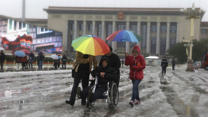 An elderly Chinese man is pushed in an wheelchair near the Great Hall of the People where the Chinese Communist Party's 18th National Congress is scheduled to begin on Nov. 8 in Beijing, China, Sunday, Nov. 4, 2012. The once-a-decade event installs a new leadership to run the world's second largest economy and newly assertive global power.  (AP Photo/Ng Han Guan)