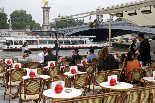 People sit at a terrace cafe on the opening day of the new pedestrian walkway area between Orsay museum and Alma bridge on the left bank of the River Seine in Paris
