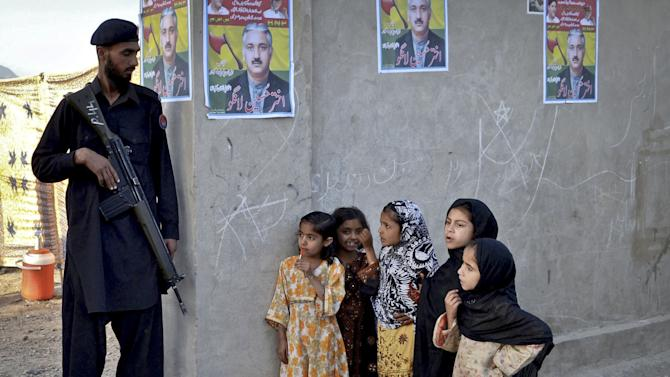 "In this Monday, May 6, 2013 photo, Pakistani children look at a soldier standing guard at an entrance of a  compound where an election rally is held in Quetta, Pakistan. The graffiti on walls around this Pakistani provincial capital hold a dire warning ahead of this weekend's national elections, ""Voting means death."" It's a very real threat: Over recent weeks at least six people have been killed and nearly 40 wounded in bombings and grenade attacks targeting candidates. (AP Photo/Arshad Butt)"