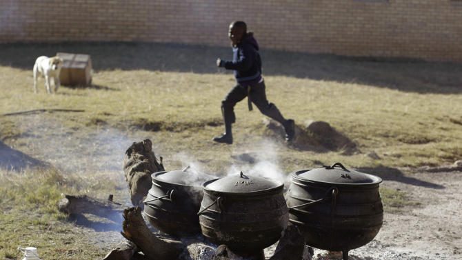 A child runs past food being cooked at the No-Moscow school for celebrations for former South African president Nelson Mandela in Qunu, South Africa, Tuesday, July 17, 2012. South African's will celebrate former president Nelson Mandela's birthday tomorrow. (AP Photo/Schalk van Zuydam)