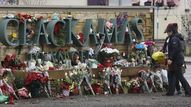 File--In this Dec. 19, 2012, file photo, two women deliver flowers and a balloon to the Clackamas Town Center mall entrance in Portland, Ore., a week after a gunman opened fire in the mall, killing the two people and himself.   Law authorities released a 950-page report, Wednesday, May 1, 2013, on the shooting where a gunman blazed away with a military-style semiautomatic rifle as people did their Christmas shopping. (AP Photo/Don Ryan, file)