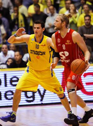 In this Sunday, Dec. 2, 2012 photo, Maccabi Tel Aviv basketball club captain Guy Pnini, left, and Hapoel Tel Aviv player Jonathan Skjöldebrand, play during a match between the clubs in Tel Aviv. Israel's premier basketball team has suspended its captain because he called a rival Israeli player a Nazi. Pnini told local media that he had lashed out at the rival player during a match earlier this week, after that player physically and verbally taunted him. (AP Photo/Nir Keidar)