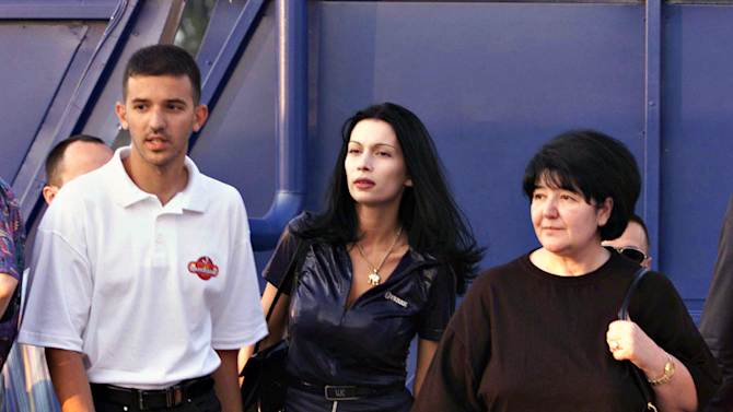 FILE - A July 4, 1999 file photo of former Yugoslav President Slobodan Milosevic's family, wife Mirjana Markovic, right, son Marko Milosevic, left, and Milica Gajic, Marko's common law wife, center, at the opening of Bambi amusement park in Pozarevac, Serbia. A senior Serbian official says Slobodan Milosevic's widow and son should return from their exile in Russia now that the former autocrat's allies have returned to power in the Balkan country. Milosevic's widow, Mirjana Markovic, and son Marko Milosevic fled to Russia after the wartime leader was ousted in 2000. They have been granted refugee status there, despite warrants for their arrest issued by the former pro-Western Serbian government which was defeated by nationalists in elections in May. (AP Photo/Darko Vojinovic, File)