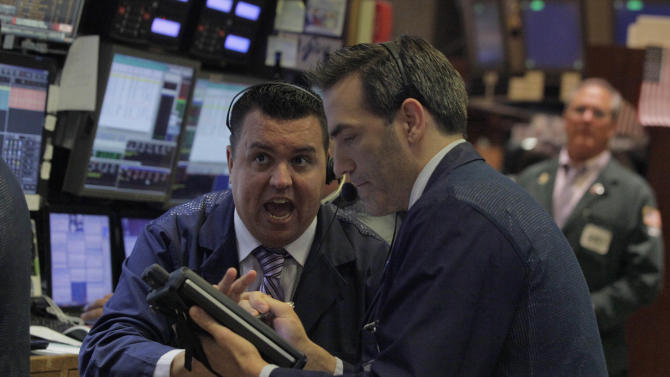 Traders Bobby Finnerty, left, and Gregory Rowe, work on the floor of the New York Stock Exchange Wednesday, Aug. 1, 2012. Stocks are mostly higher in morning trading. (AP Photo/Richard Drew)